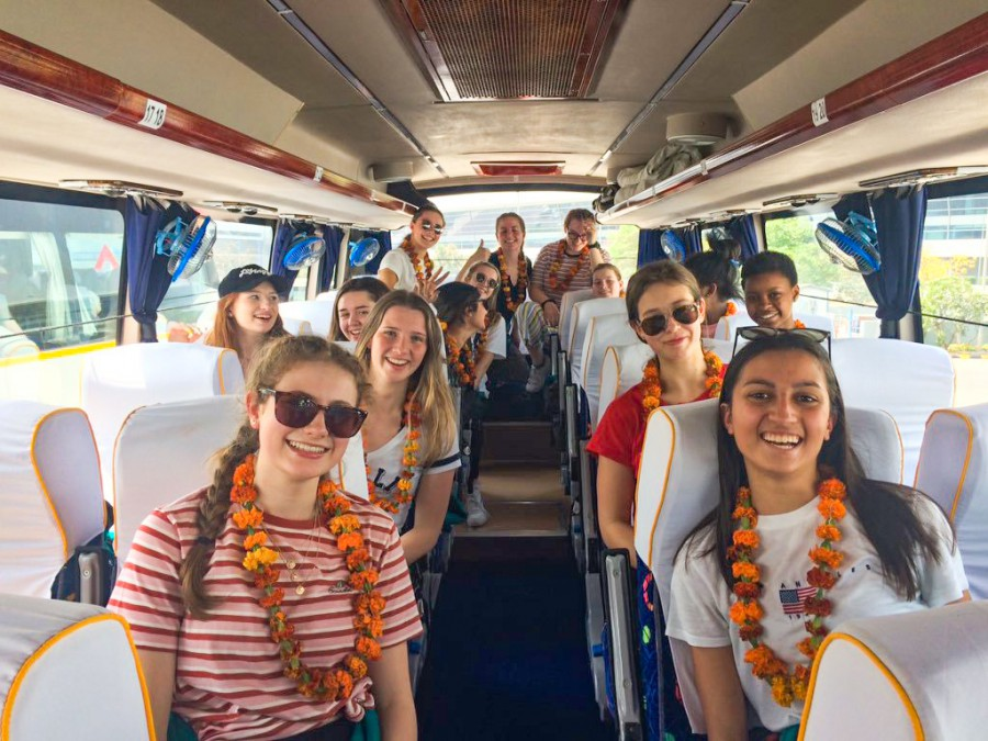 Students on coach in India marigold leis