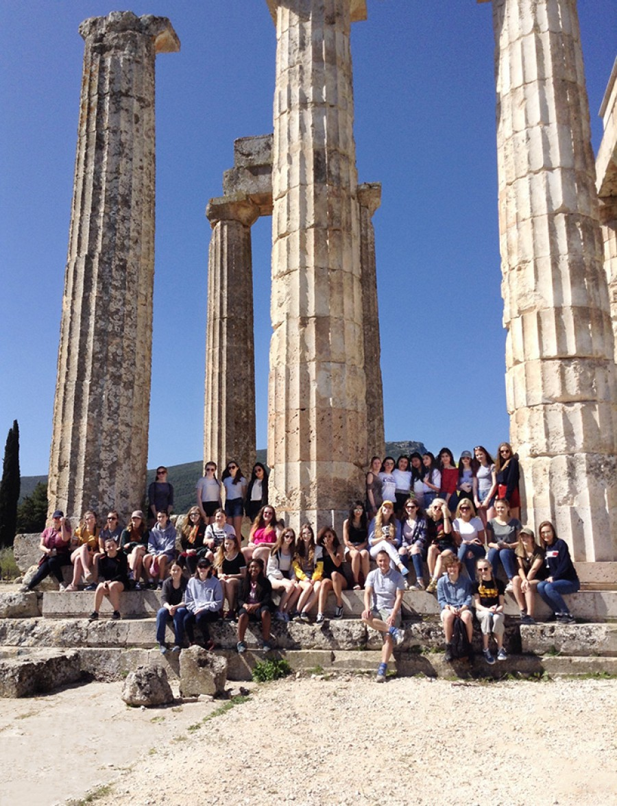 Students sitting by Greek columns